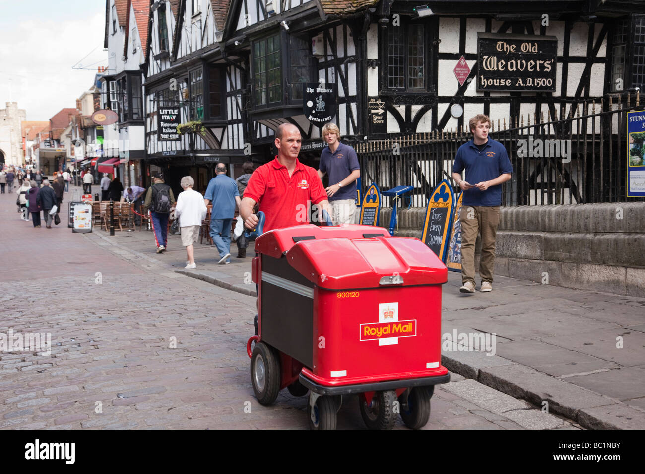 A Postman pushing a Royal Mail post trolley delivering mail in a city street. Canterbury Kent England UK Britain - Stock Image