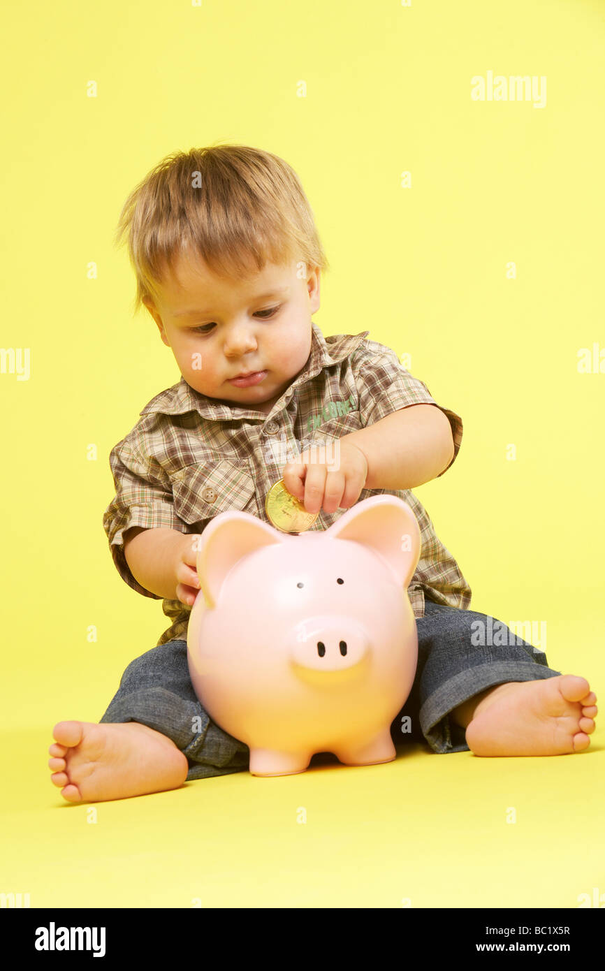 Toddler In Studio With Piggy Bank Stock Photo