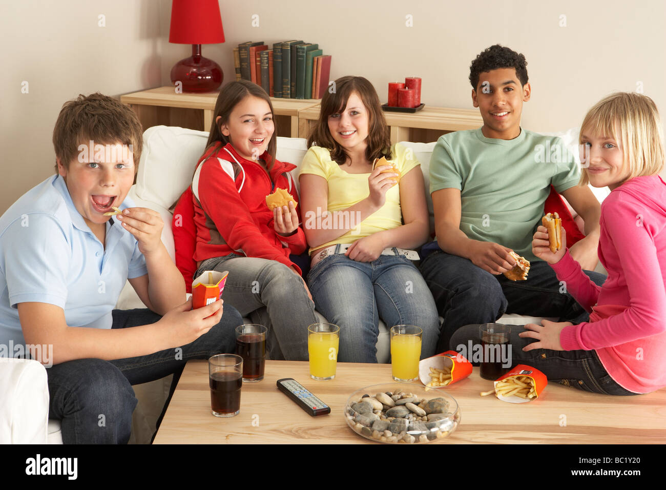 Group Of Children Eating Burgers At Home - Stock Image