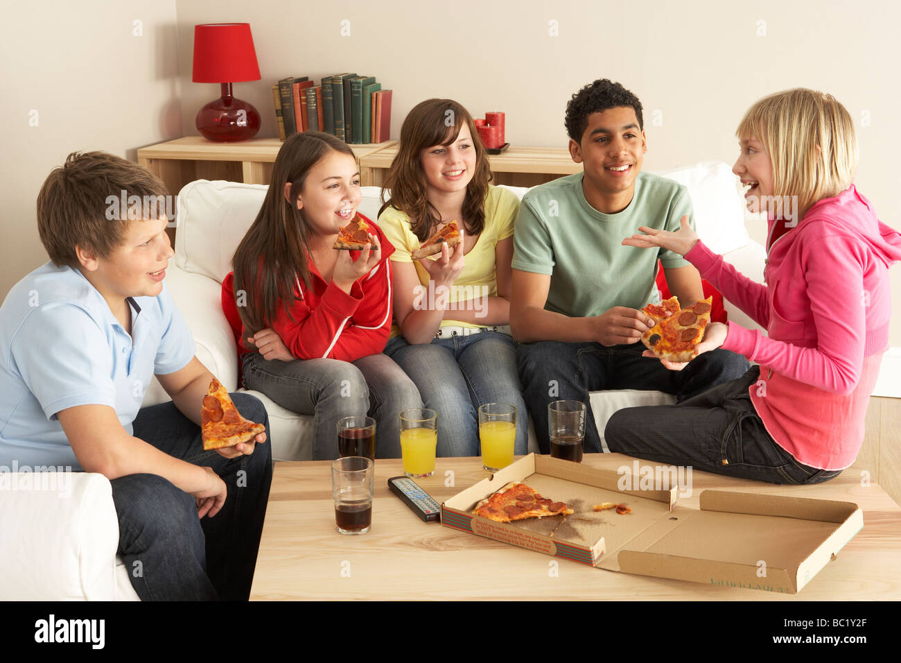 Group Of Children Eating Pizza At Home - Stock Image