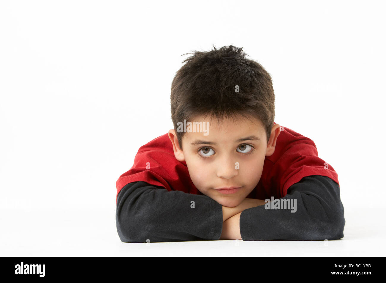 Young Boy Lying On Stomach In Studio - Stock Image
