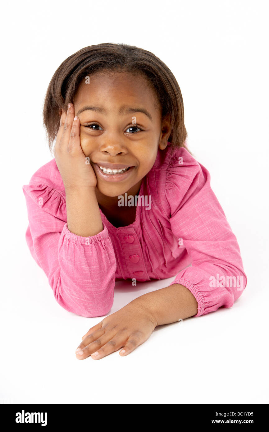 Young Girl Lying On Stomach In Studio - Stock Image