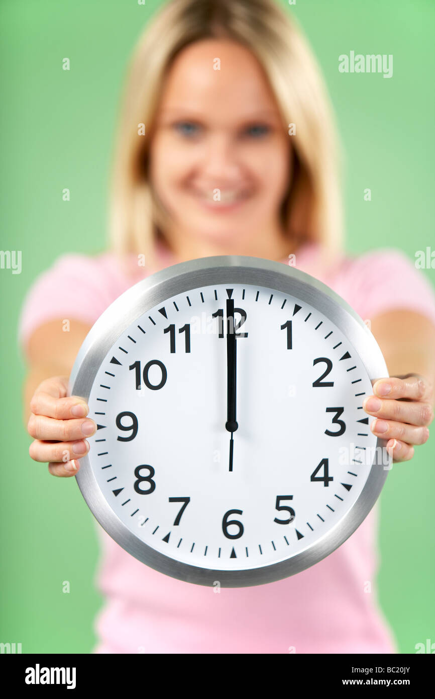 Woman Holding Clock Showing 12 O'Clock - Stock Image