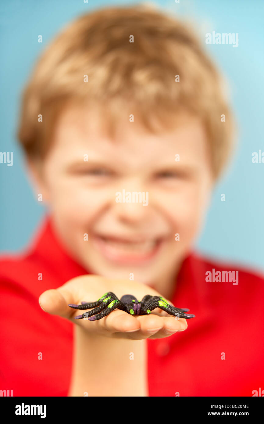 Young Boy Holding Plastic Spider - Stock Image