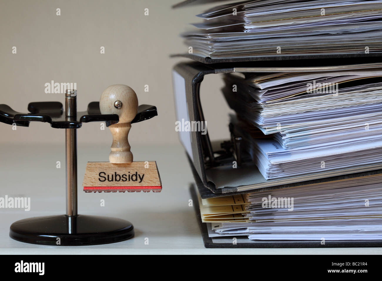 Stamp with inscription Subsidy next to a pile of files - Stock Image