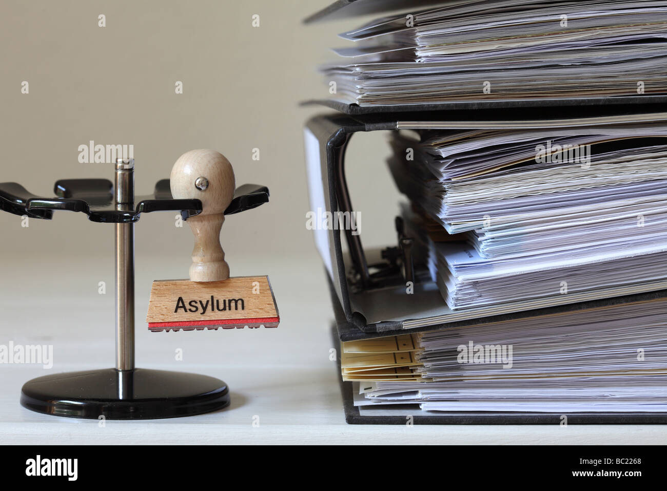 Stamp with inscription Asylum next to a pile of files - Stock Image