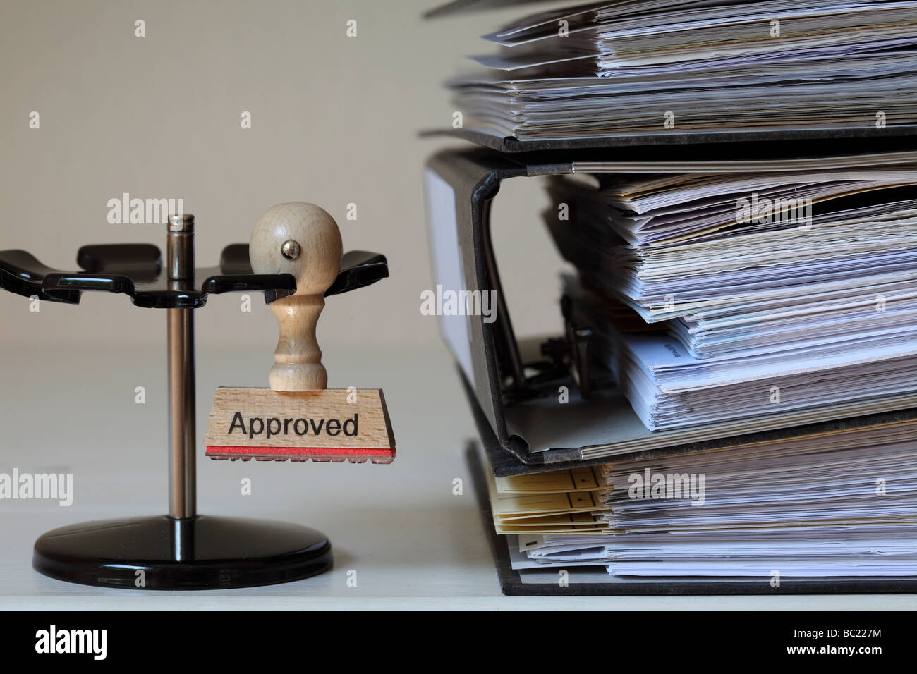 Stamp with inscription Approved next to a pile of files - Stock Image