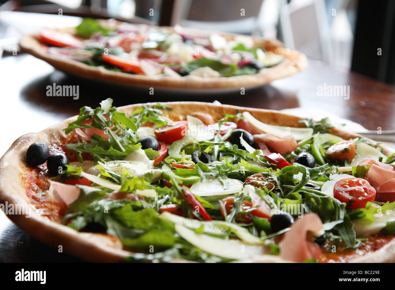 Two pizzas that look tempting and delicious ready for eating. Stone baked thin crust - Stock Image