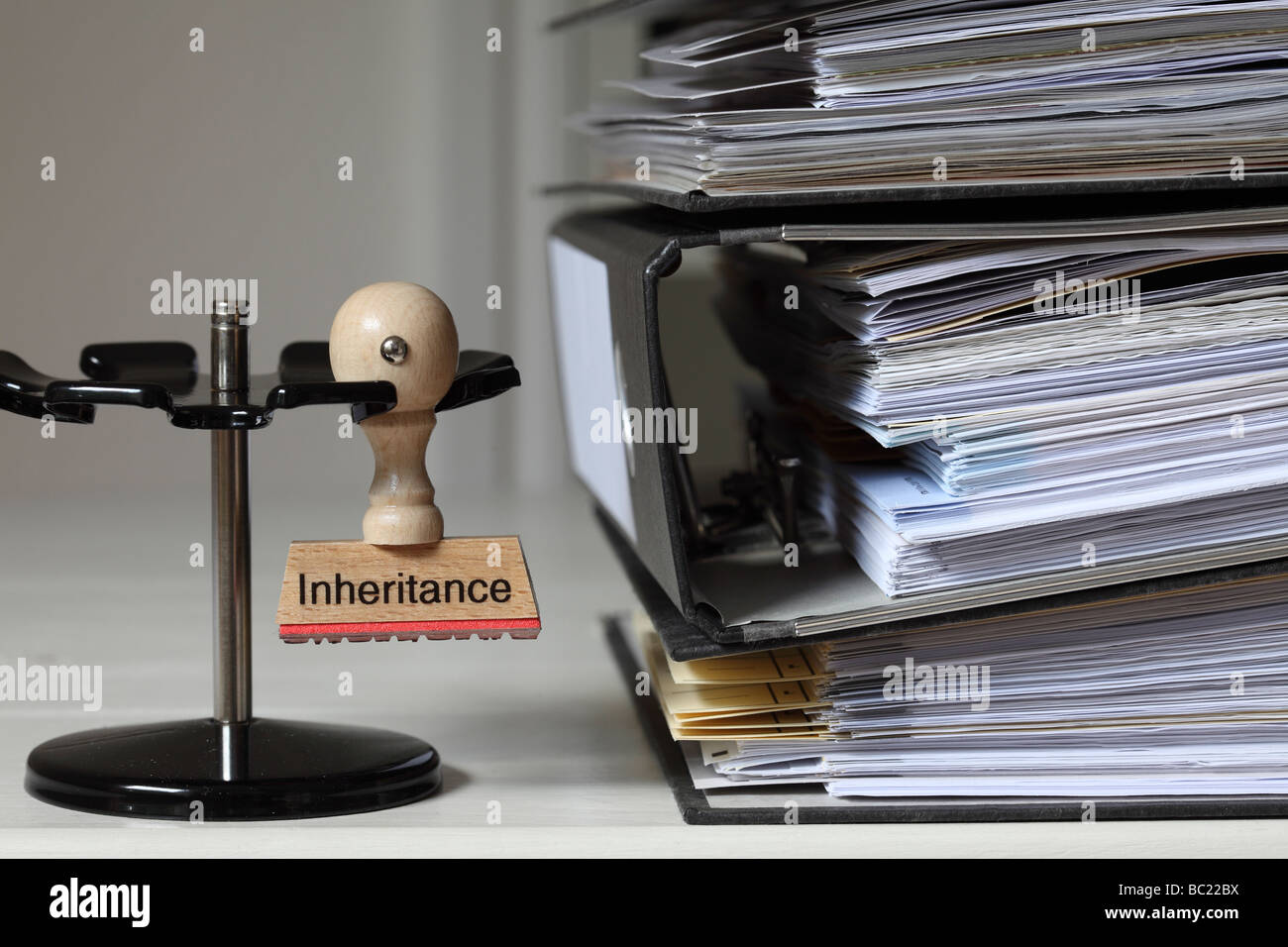 Stamp with inscription Inheritance next to a pile of files - Stock Image
