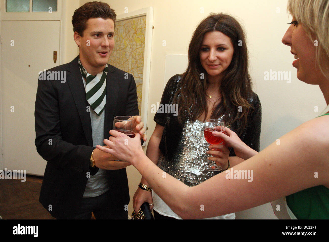 Guests are presented with drinks at the entrance to a party (a pop up dinner). - Stock Image