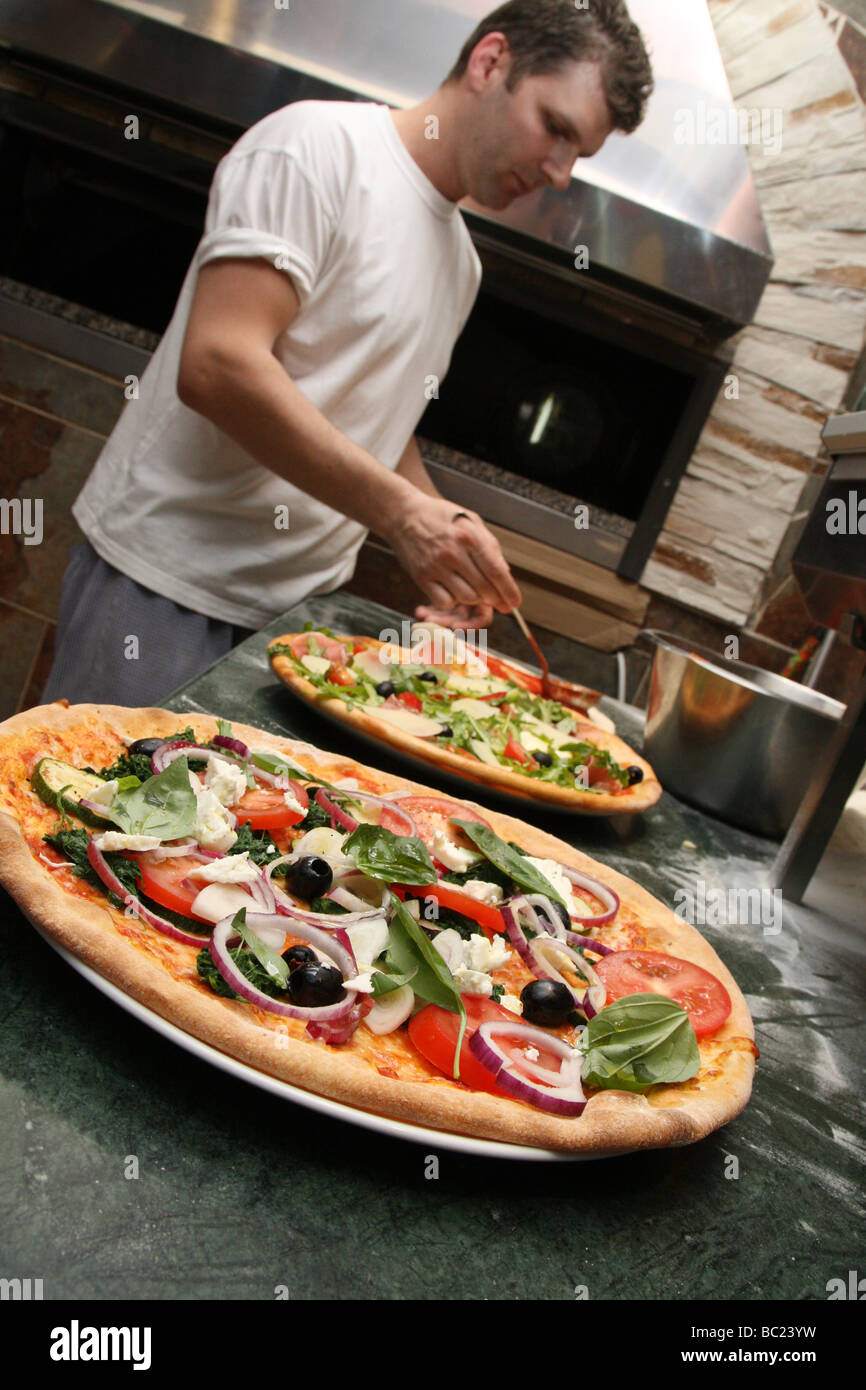 Pizzas topped with delicious looking vegetables made by chef in a restaurant - Stock Image