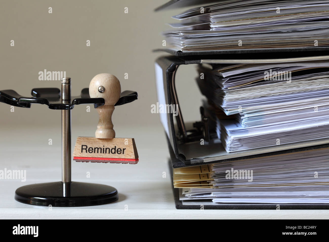 Stamp with inscription Reminder next to a pile of files - Stock Image