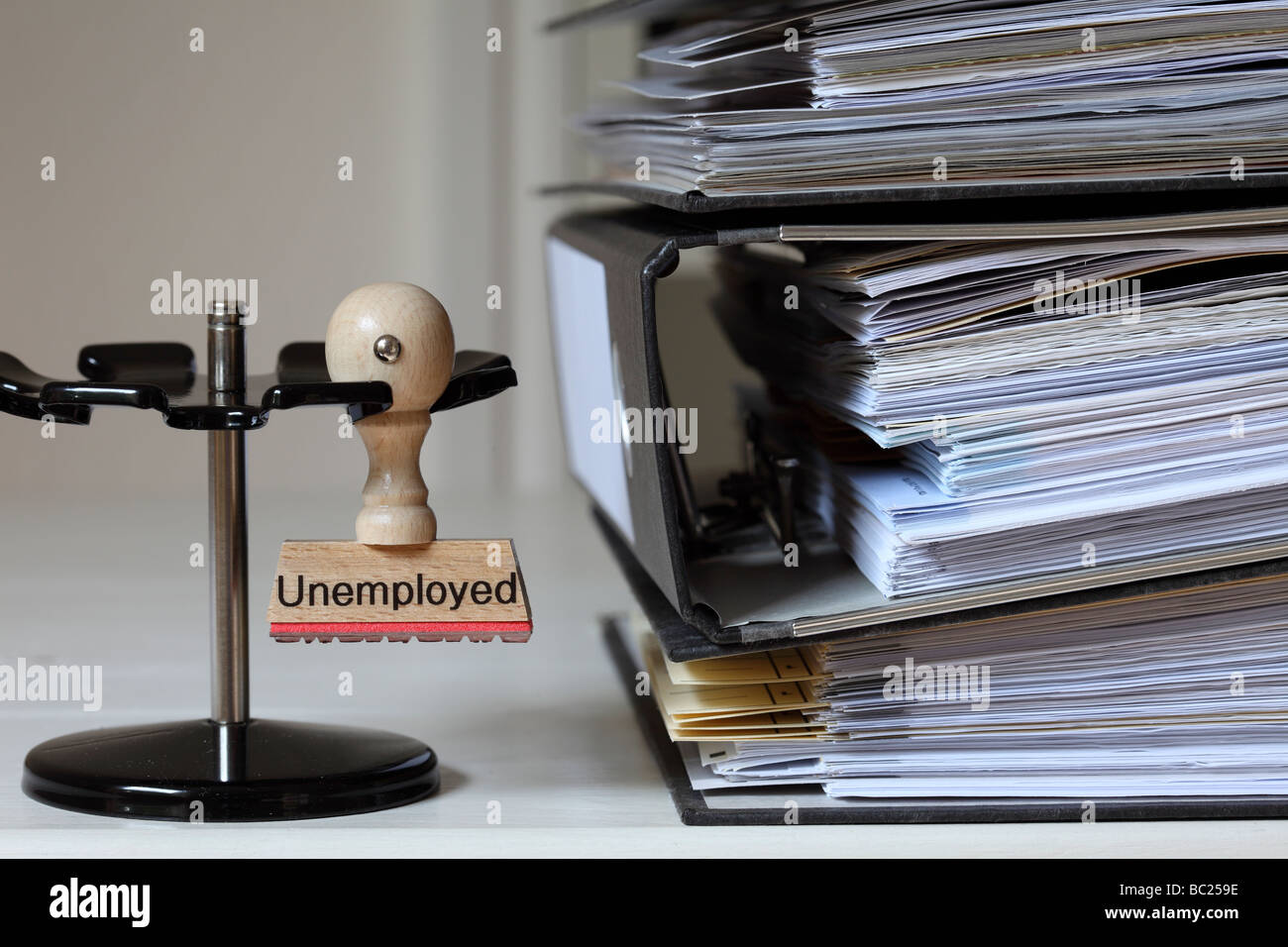 Stamp with inscription Unemployed next to a pile of files - Stock Image