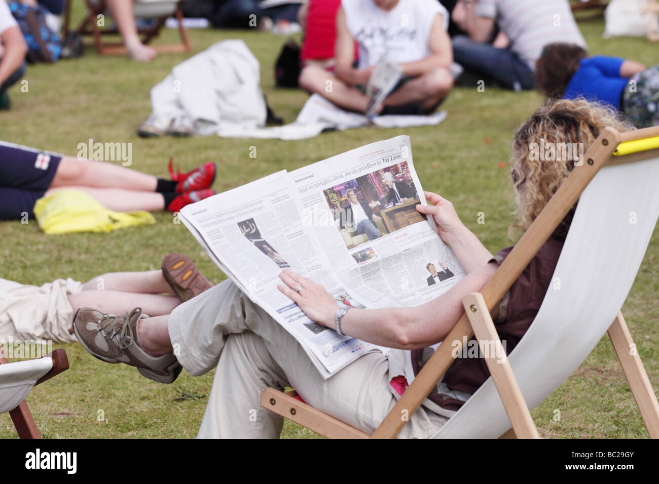 Hay Festival woman relaxing reading a newspaper sat in a deckchair on the grass lawns at the Hay Festival May 2009 - Stock Image