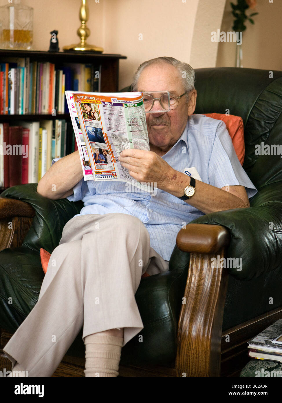 Old Man Sits In His Favourite Armchair Reading The