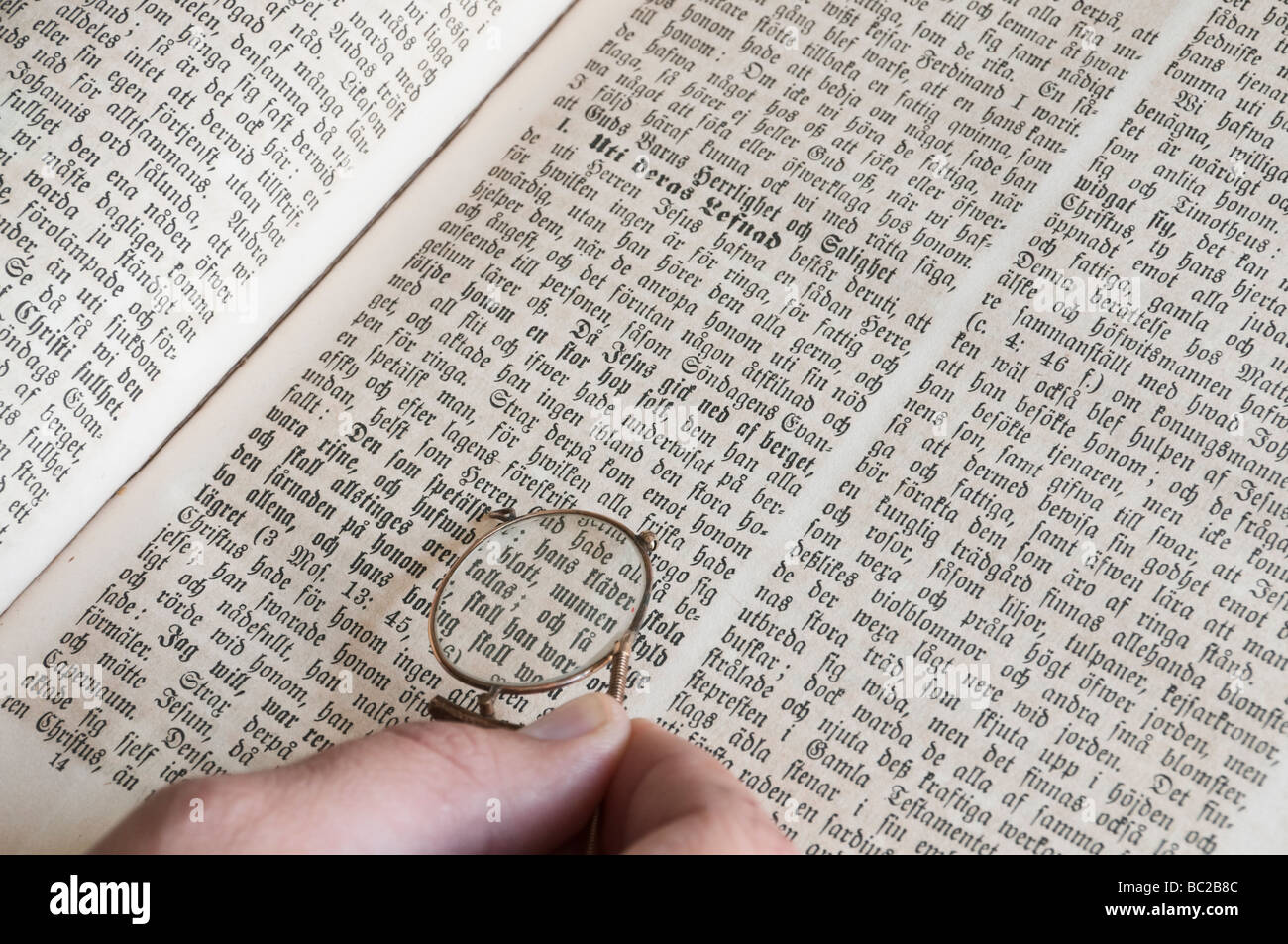 Hand holding a pair of pince-nez eye-glasses over Swedish bible. Stock Photo