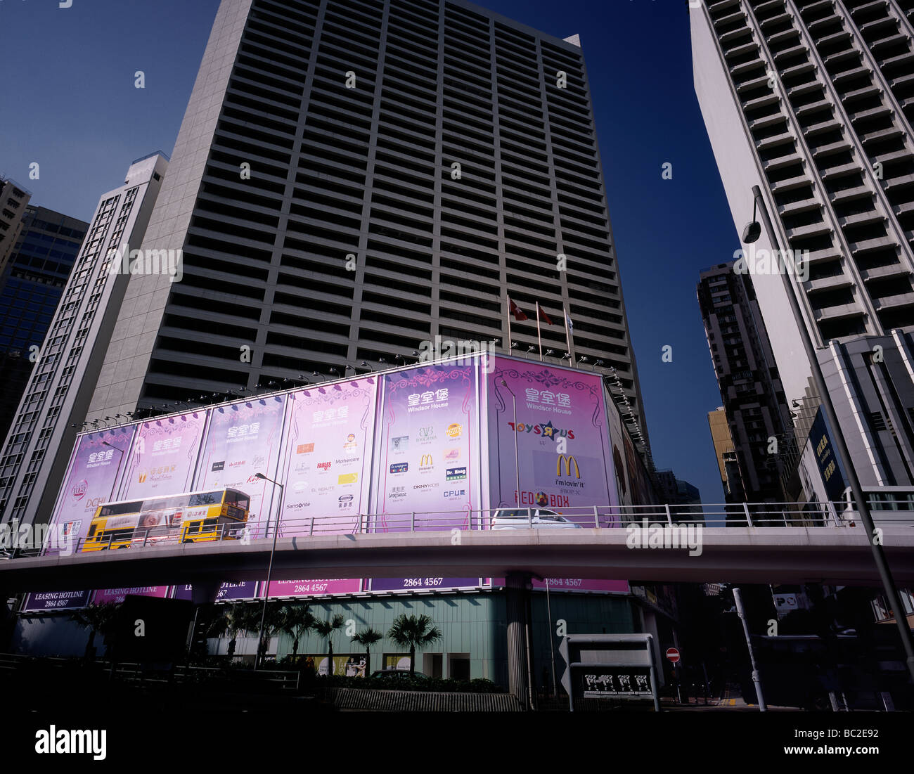 Yellow double-decker bus passing large billboards at an overpass in Hong Kong, China. - Stock Image