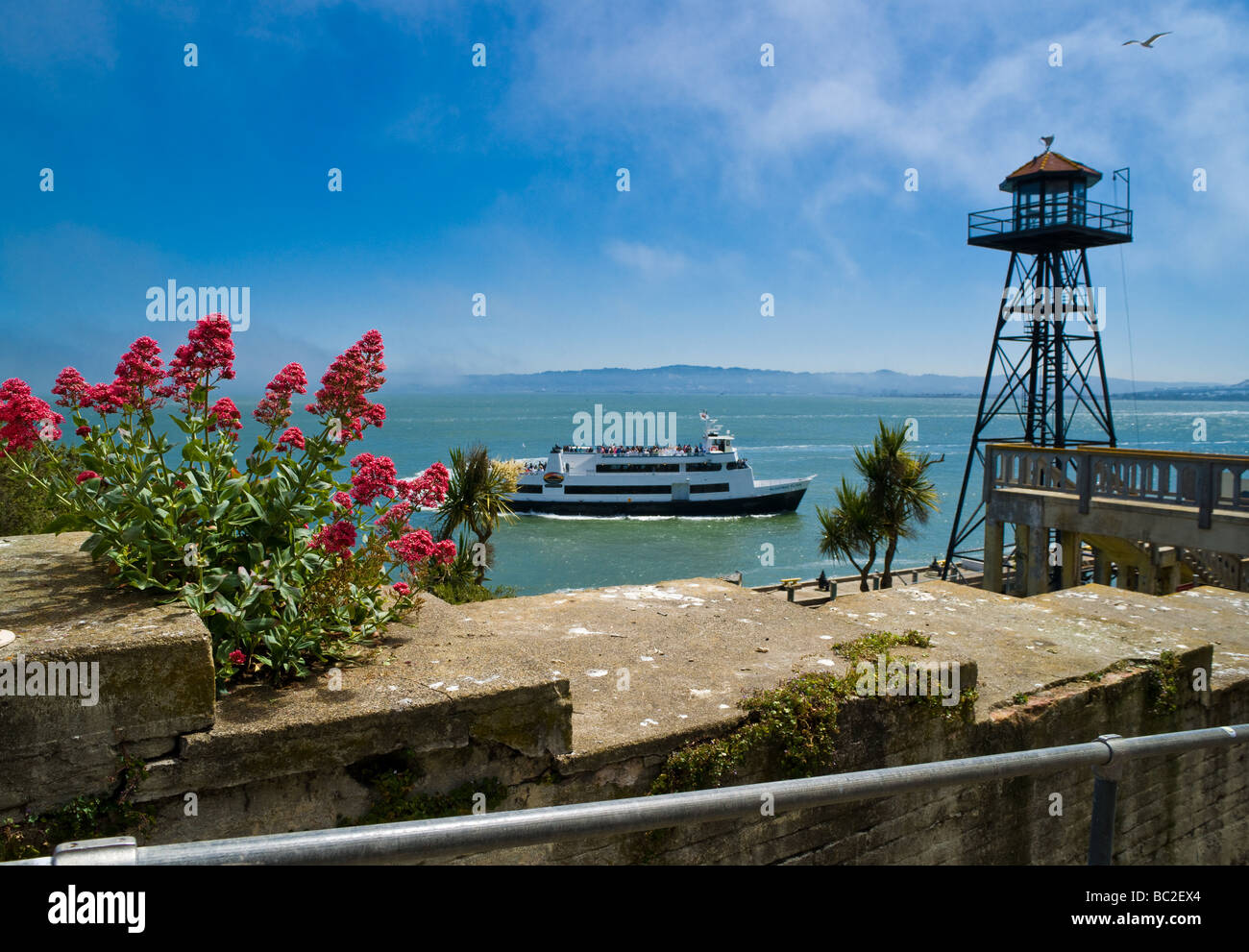 A tour boat passes behind a guard tower as it delivers visitors to Alcatraz. - Stock Image