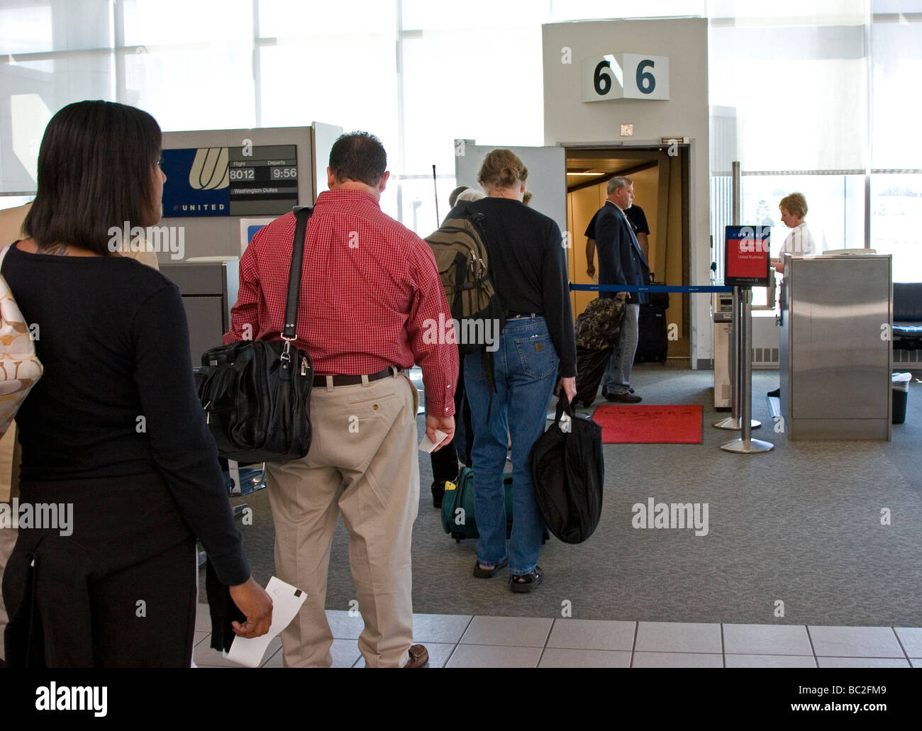 Passengers line up at airport gate to board plane - Stock Image