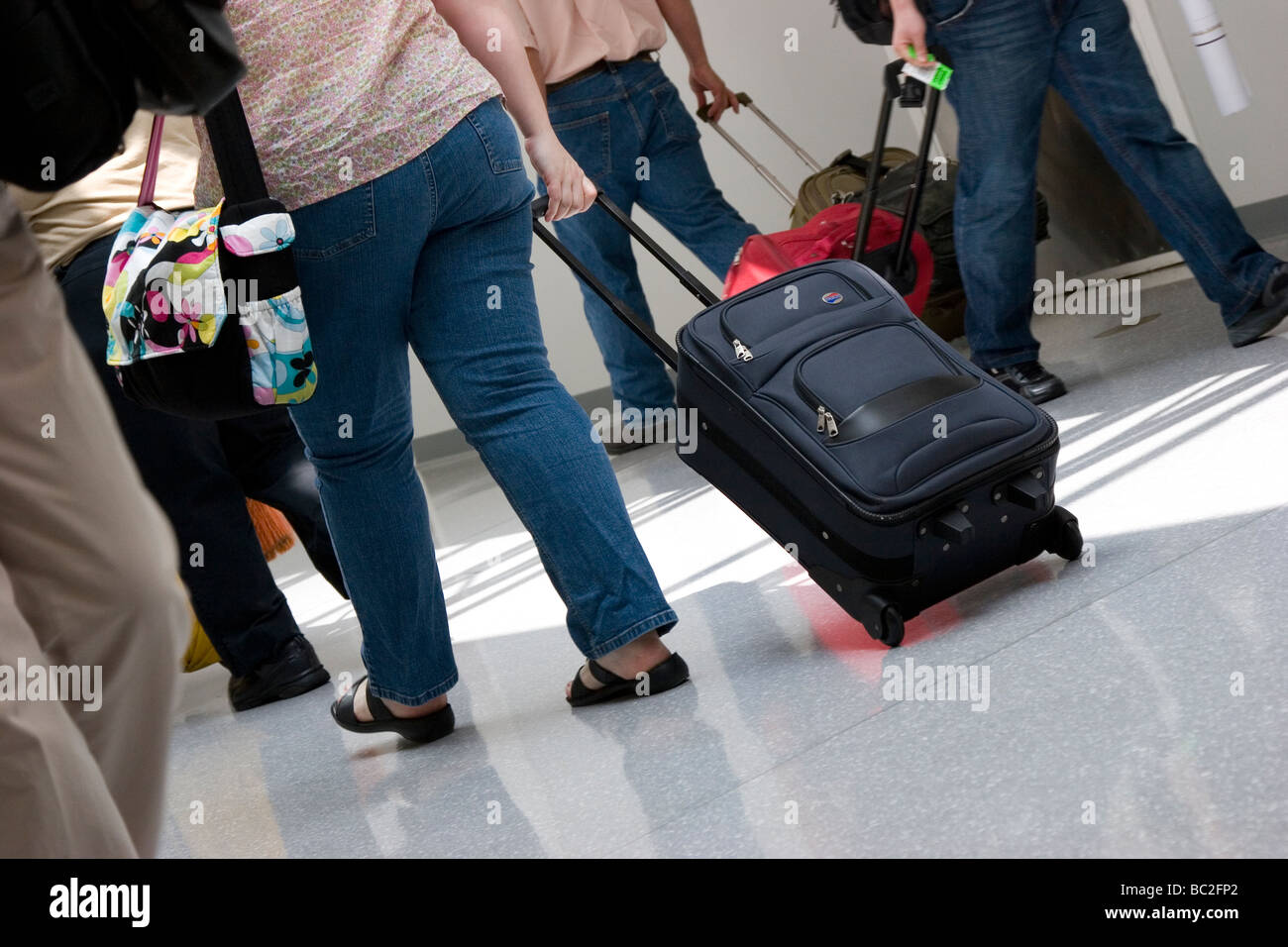 Passengers pull luggage through airport terminal - Stock Image