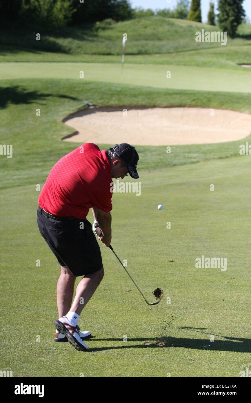 A golfer with a great swing takes a perfect divot while hitting an approach golf shot to a green and flagstick in - Stock Image