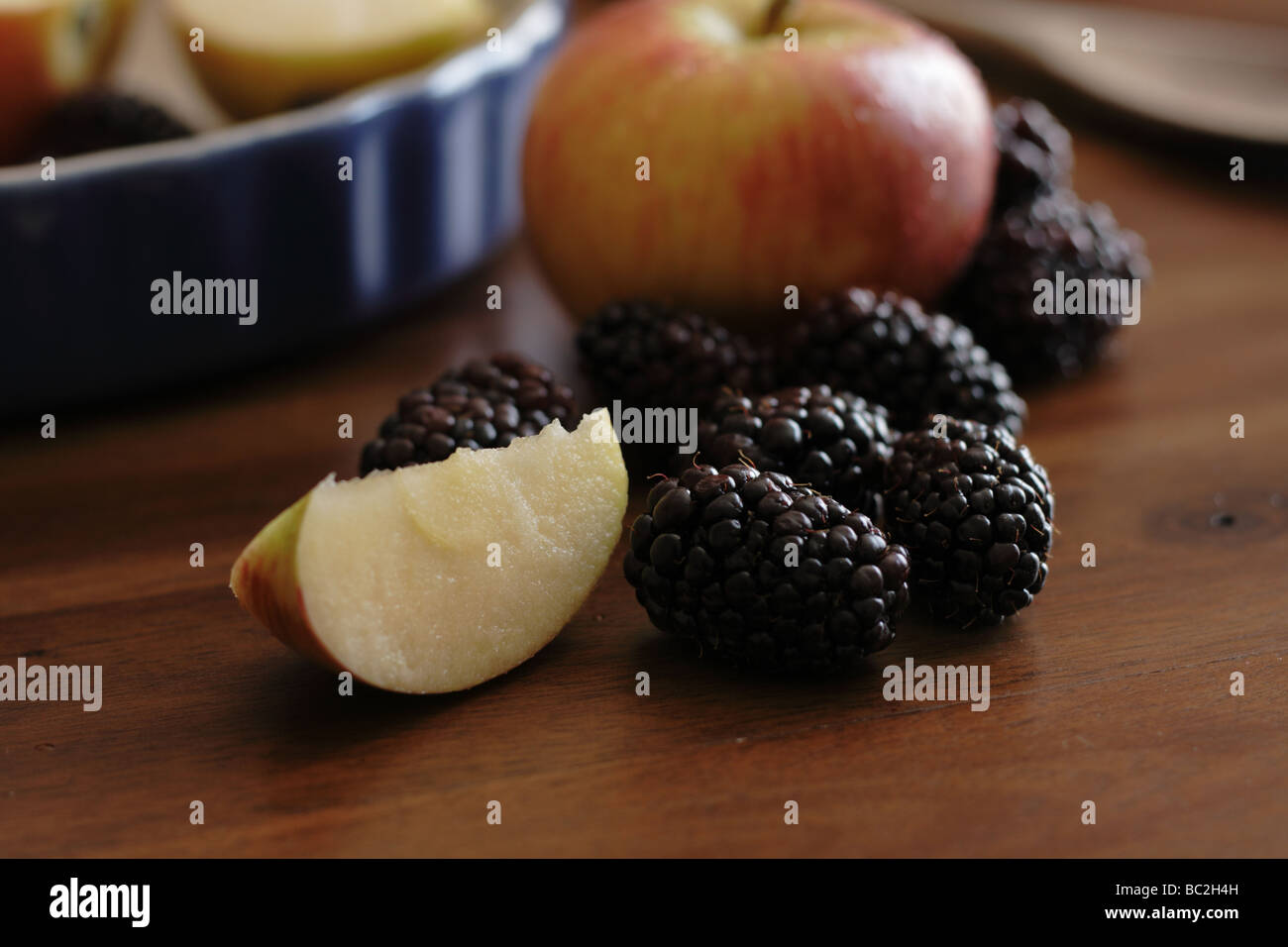 Apples and blackberries on a wooden table - Stock Image