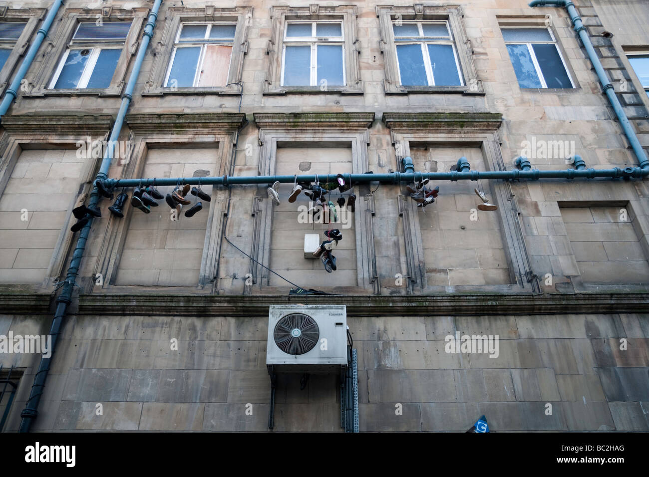 A collection of shoes hanging from a drain pipe on the back of a building - Stock Image