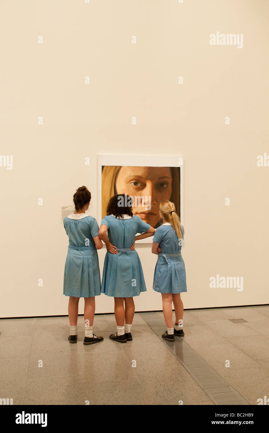 National Gallery of Victoria, Schoolgirls looking at a painting of a girl's face, Melbourne, Victoria, Australia - Stock Image
