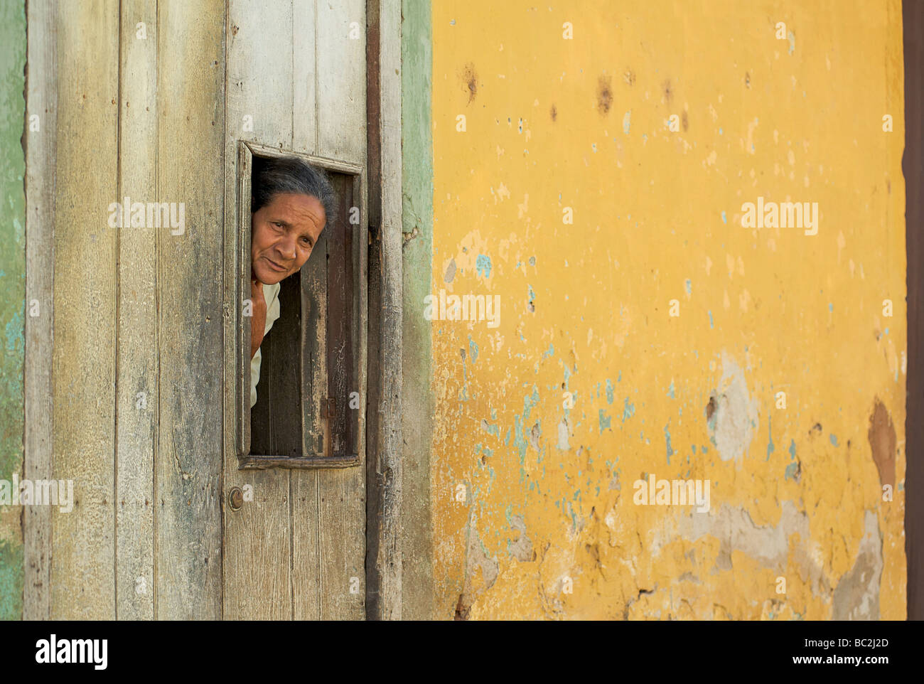 Cuban woman peering from a hatch in the door to her brightly painted colonial home. Trinidad, Cuba Stock Photo