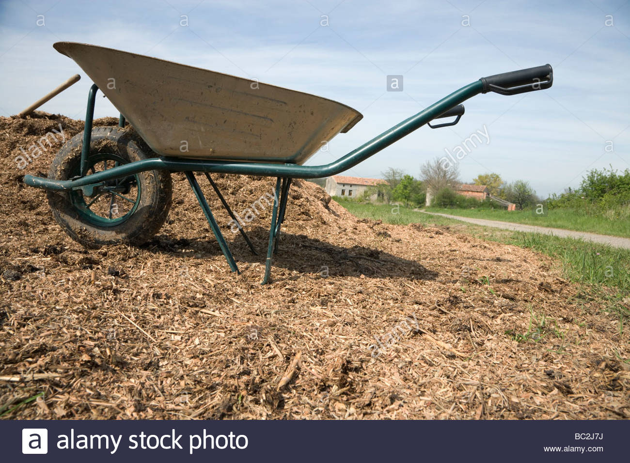 wheelbarrow at a heap with wood chips - Stock Image