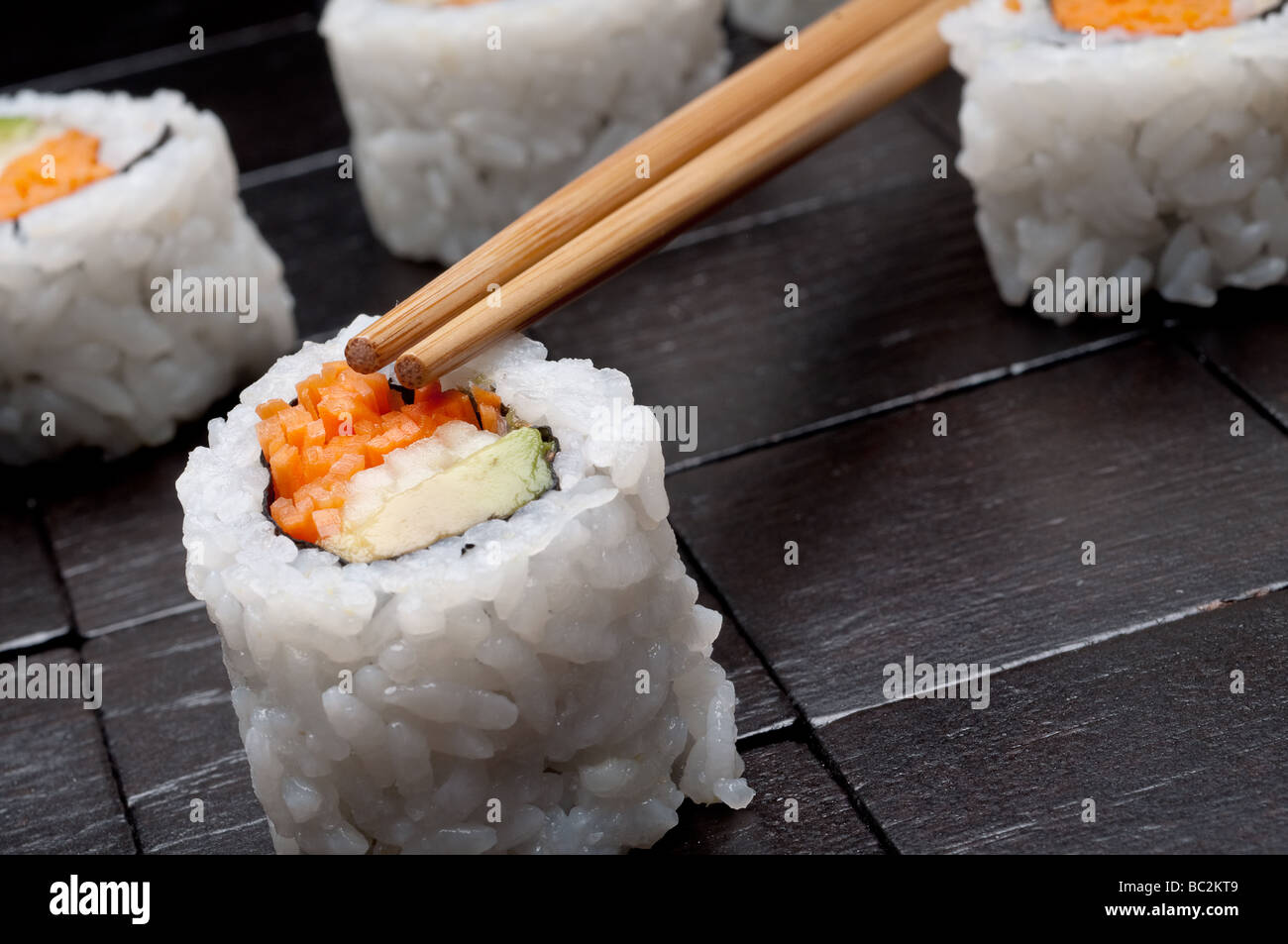 a tilted horizontal shallow focus macro of sushi with copsticks on a black wooden background - Stock Image