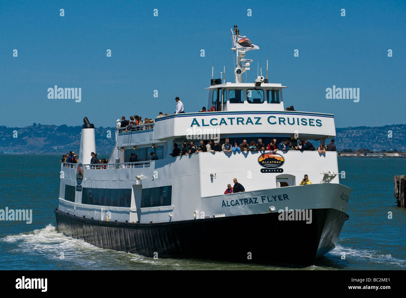 A tour boat departs the pier for Alcatraz Island. - Stock Image