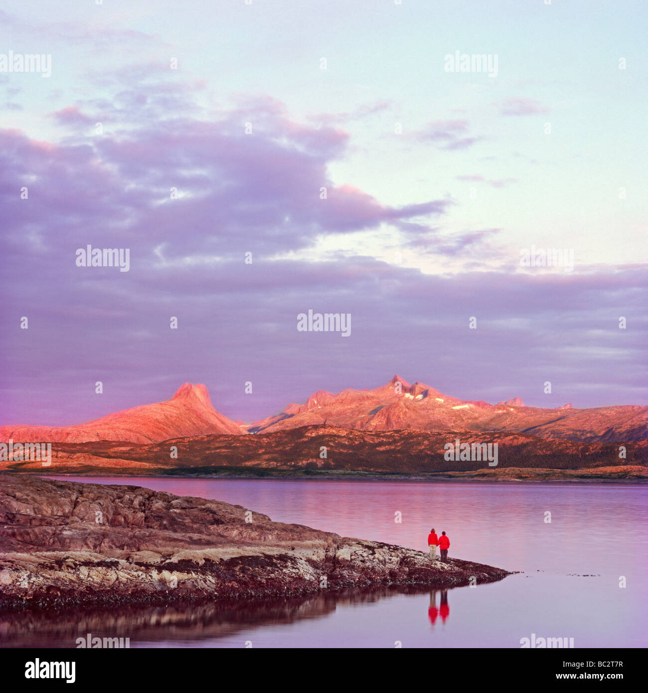 Couple waiting at fjord waterline for the last light of the day - Stock Image