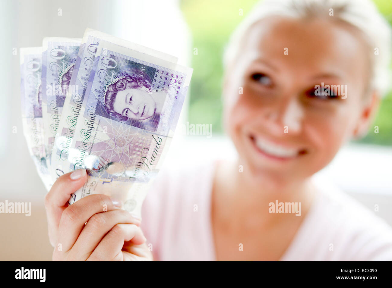 Woman holding 20 pound notes - Stock Image