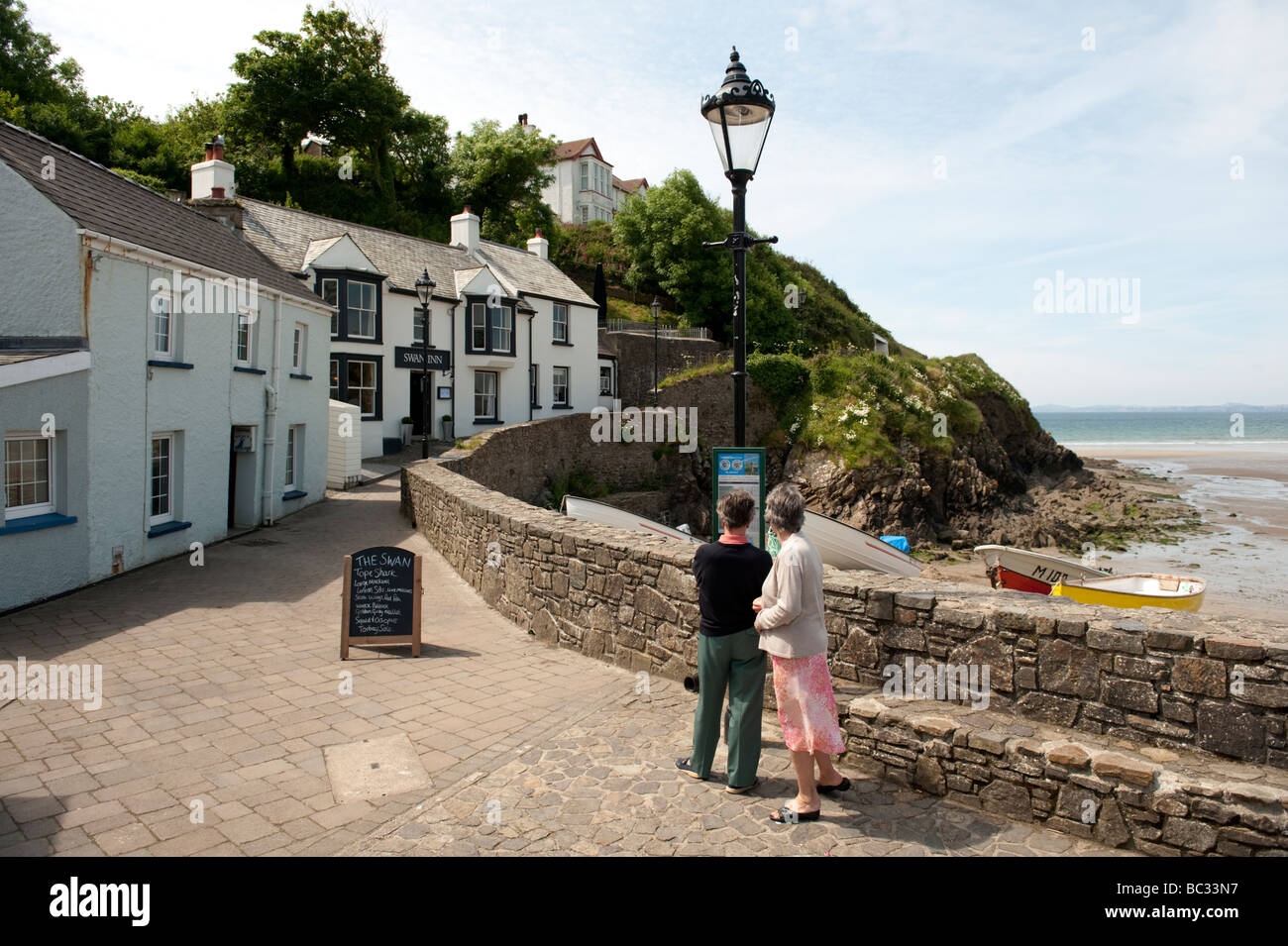 two people by the seashore on a summer afternoon Little Haven Pembrokeshire Coast National Park south west wales - Stock Image