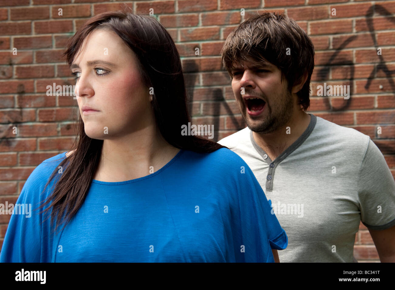 A Young couple arguing shouting relationship breakdown - boy yelling at his girlfriend who is ignoring him - Stock Image
