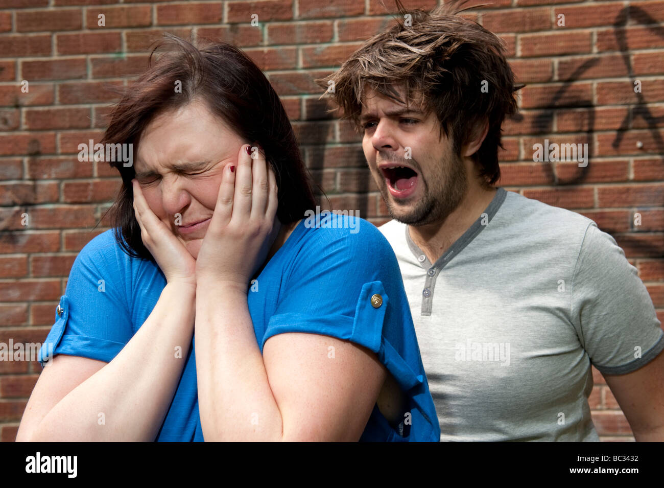 Young couple arguing shouting relationship breakdown woman holding her hands over her ears - Stock Image