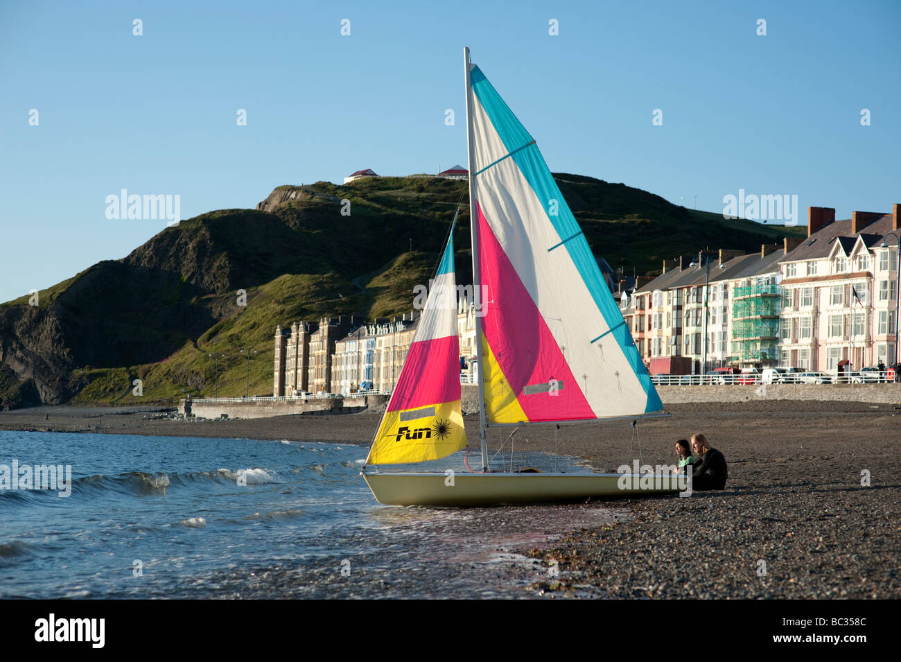 Summer evening Two people with their small sailing dinghy on the beach Aberystwyth Wales UK - Stock Image