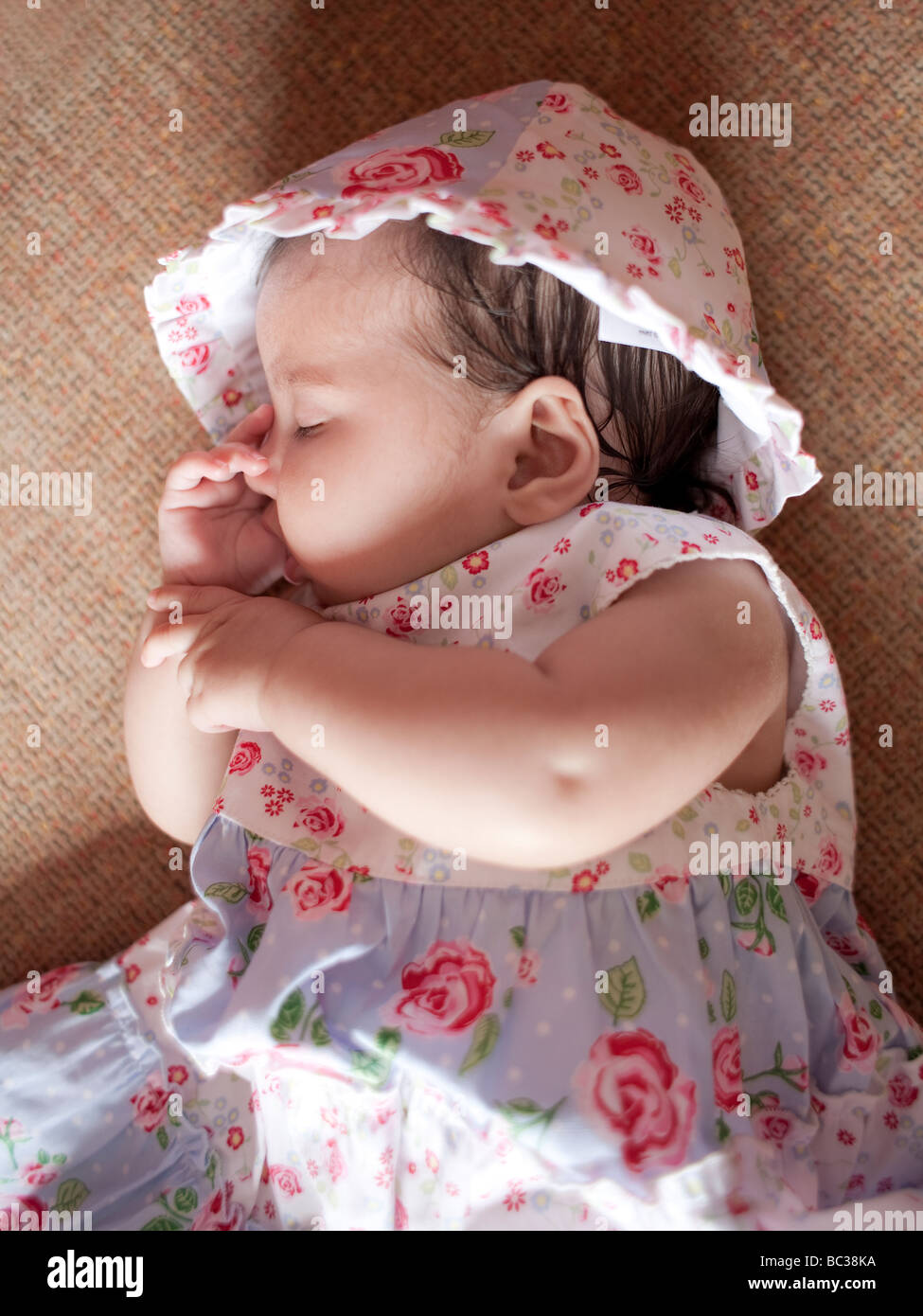 3 month old baby sleeps sucking her thumb - Stock Image