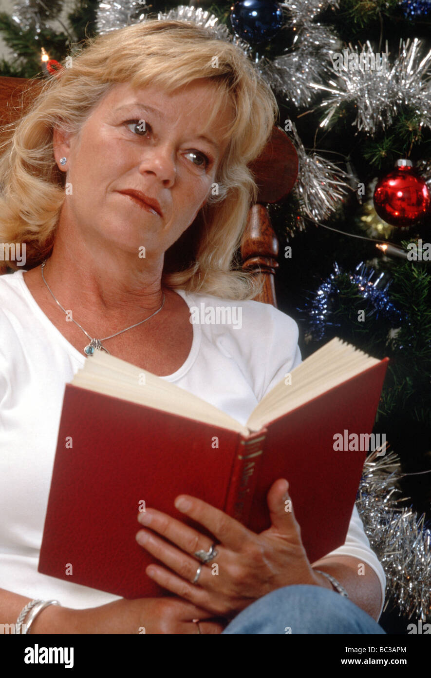 Senior woman reading book, christmas time - thinking woman   - SerieCVS100014217 - Stock Image