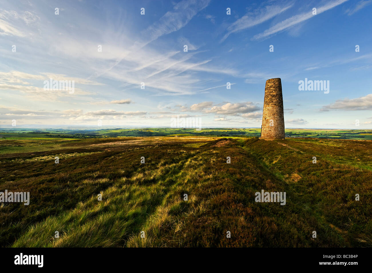 Disused chimney on moorland overlooking Allendale in North Pennines. Once used to vent fumes from lead smelting. - Stock Image
