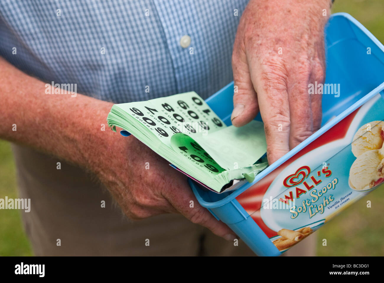 Close up of man selling raffle tickets at English village fete - Stock Image
