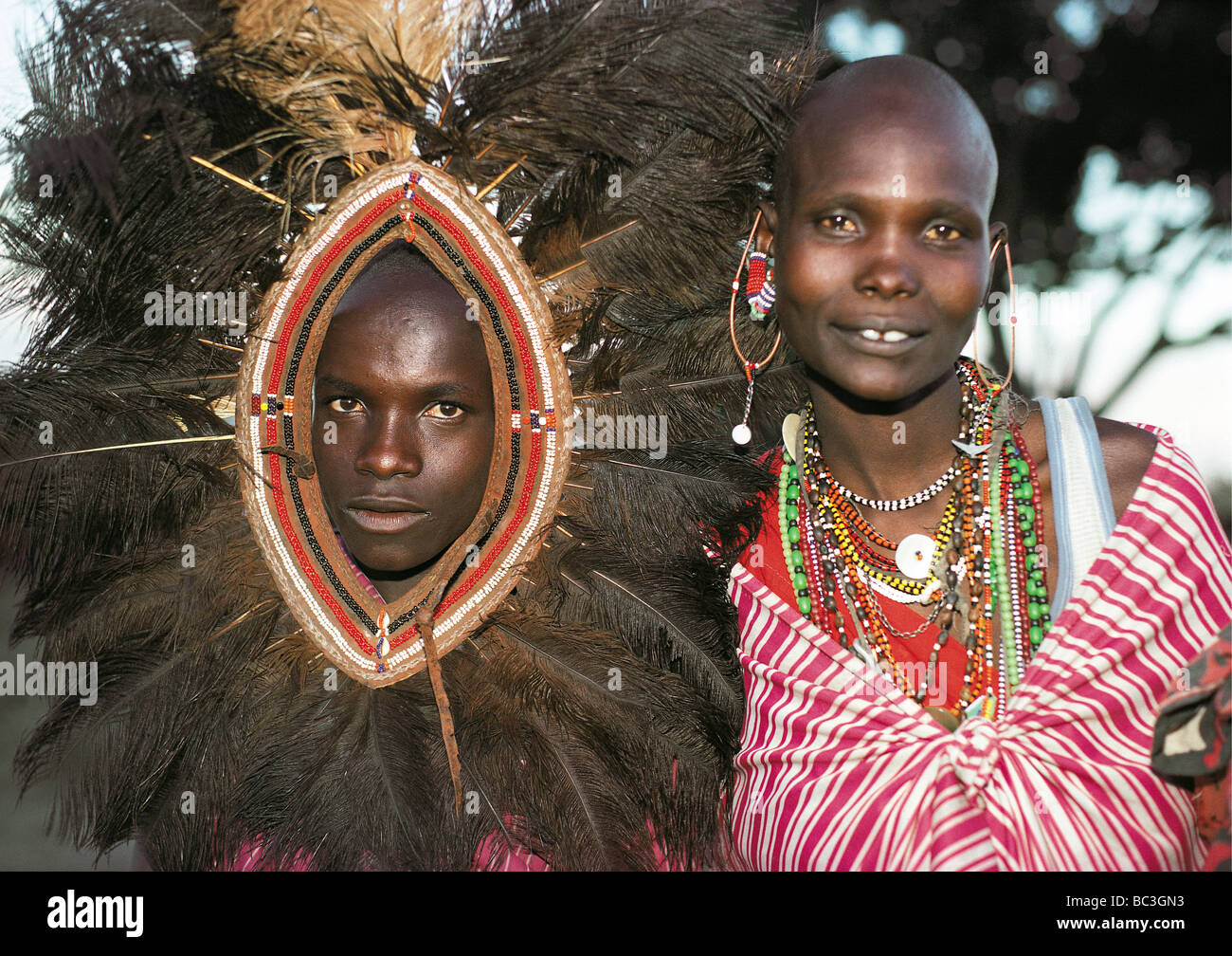 Maasai man traditional ostrich feather headdress married woman bead necklaces earrings Masai Mara National Reserve - Stock Image