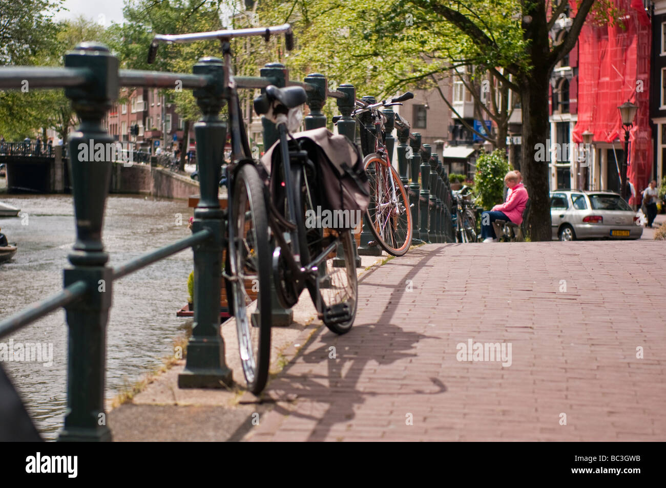 Bicycle parked against an iron railing on a bridge over a canal in Amsterdam Stock Photo