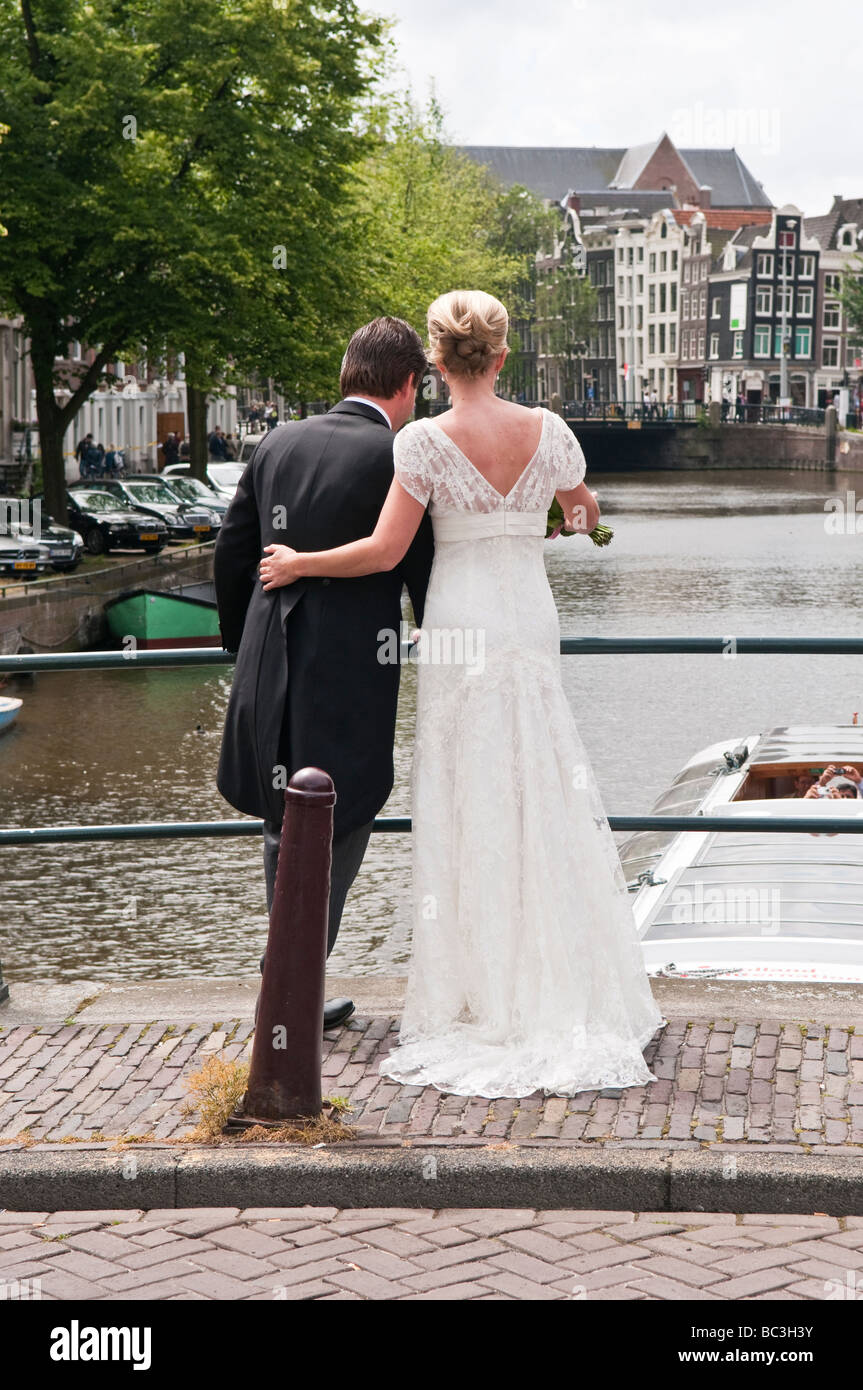 Bride and Groom stand on a bridge over the Prinsengracht canal in Amsterdam - Stock Image