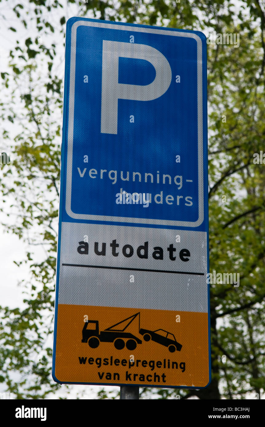 Sign stating parking is for permit holders ((vergunning-houders)  only.  Unauthorised vehicles will be towed away. - Stock Image