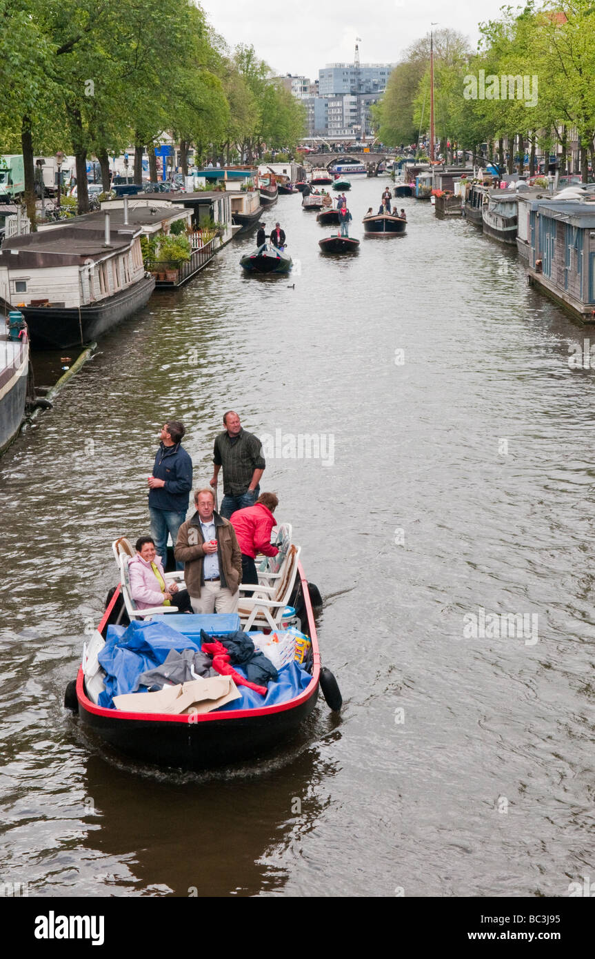 Hired boats sailing slowly past houseboats on the Prinsengracht, Amsterdam. - Stock Image