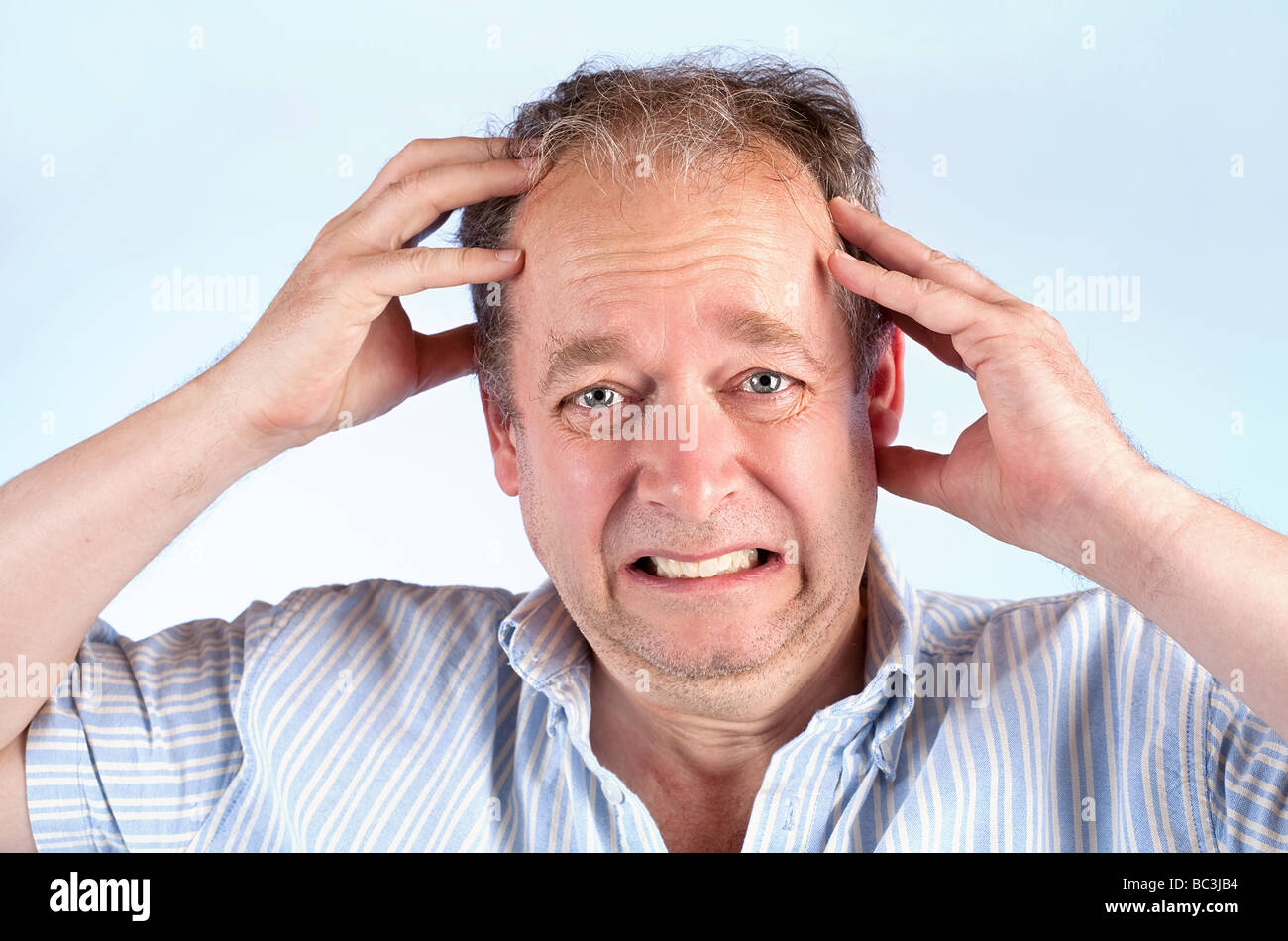 A middle-aged man is suffering from a migraine or bad news - Stock Image