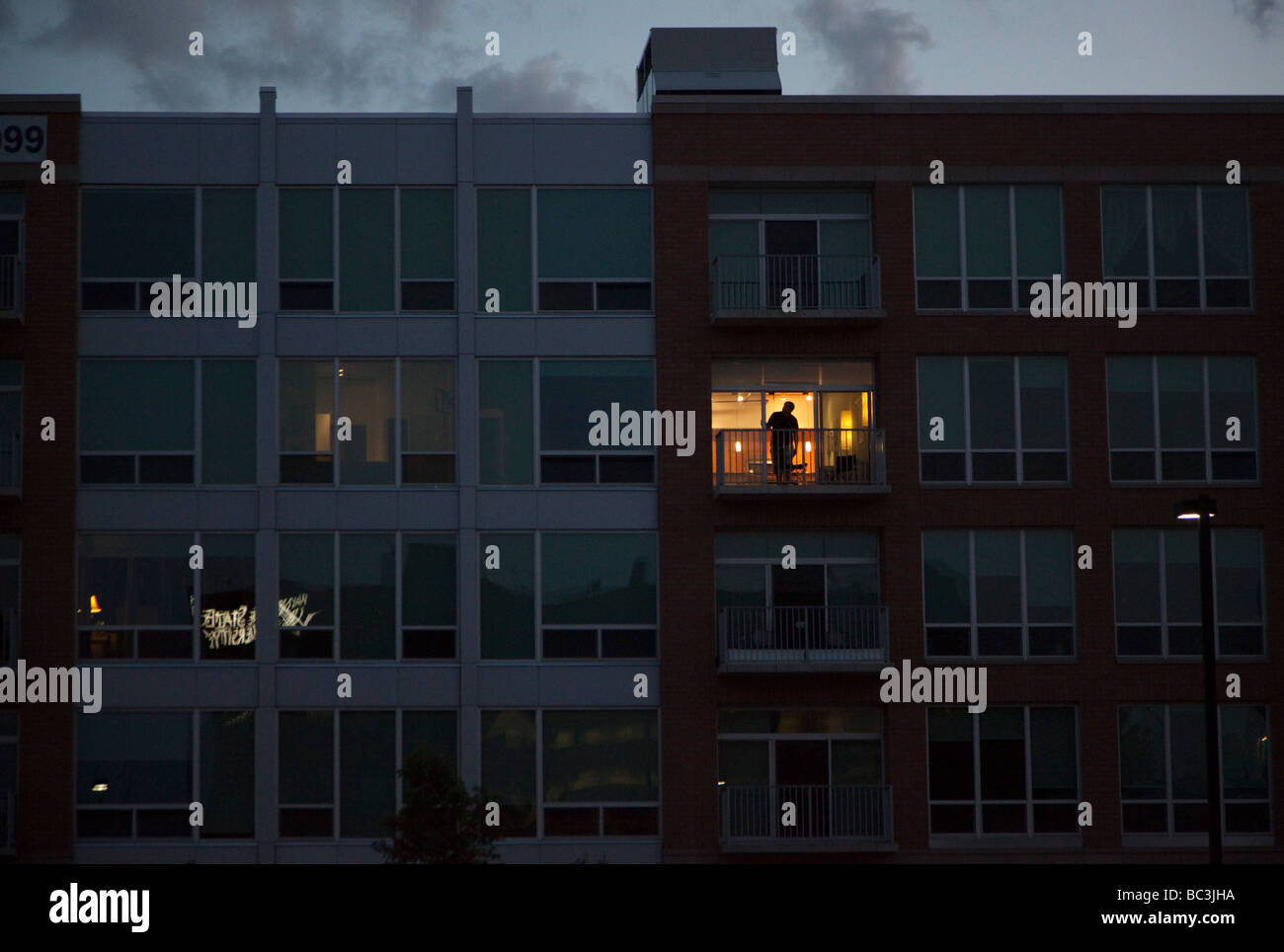 Detroit Michigan A man on the balcony of one lighted unit at The Ellington a new loft development - Stock Image
