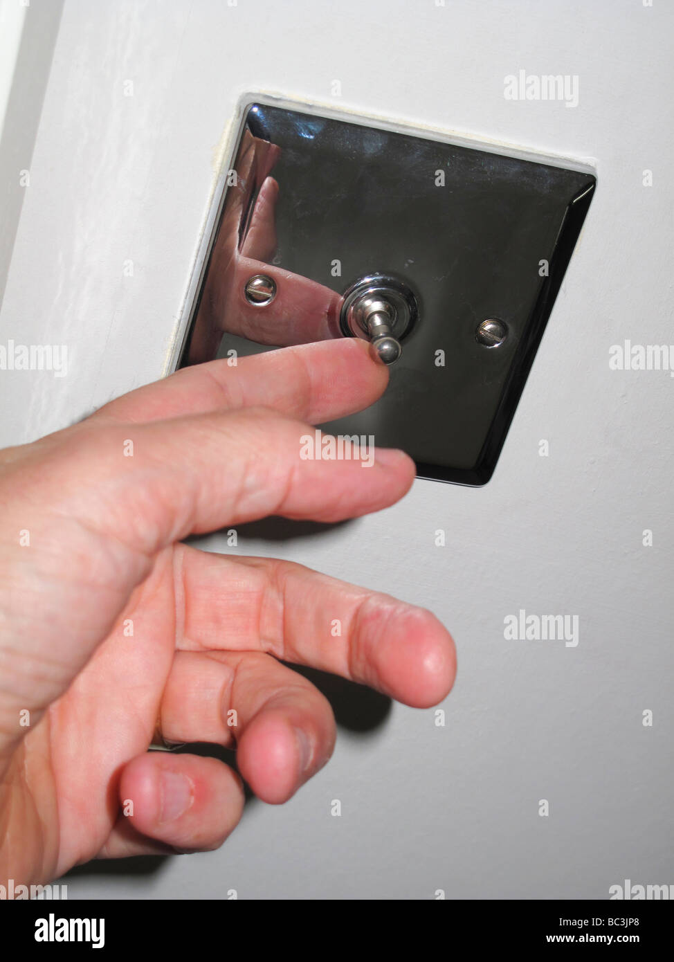 Male hand switching light switch - Stock Image